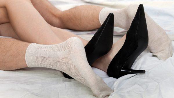 Переплетенные женские ноги в туфлях и мужские ноги в носках влюбленной пары людей, занимающихся сексом в постели